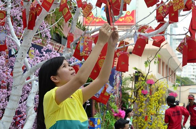 Une jeune vietnamienne accroche une enveloppe rouge. Image par bruce lam de Pixabay