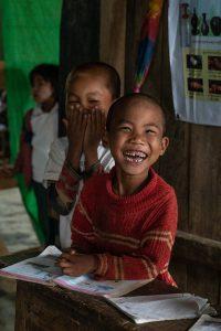 Petit garçon birman qui rigole en classe