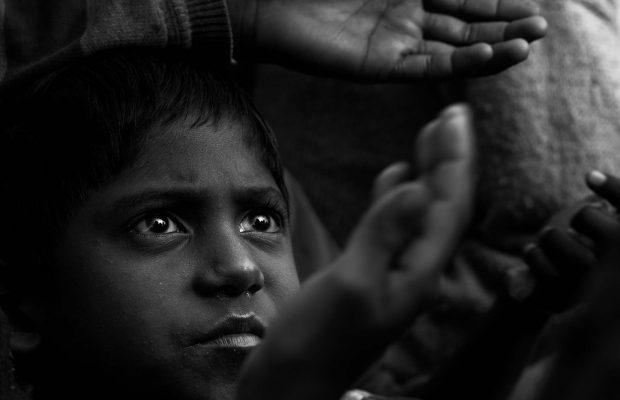 Jeune indien en noir et blanc qui tend sa main pour attraper des bonbons