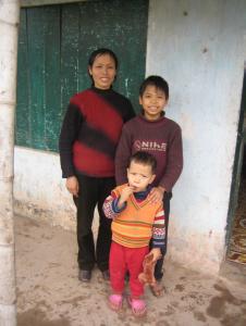 Luong, sa maman et son petit frère, devant chez eux