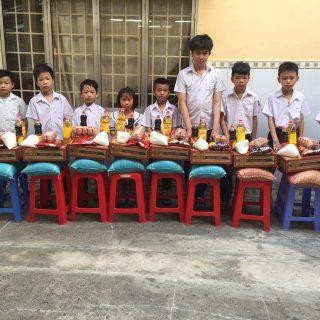 Distribution de nourriture aux enfants de Pho Cap durant la crise du Covid-19, chaque enfant recevant un paquet de riz, de l'huile, des œufs et autres denrées indispensables.