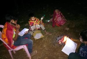 Devant le foyer, des jeunes étudient à la lampe torche après le coucher du soleil. Leur motivation est un bel exemple.