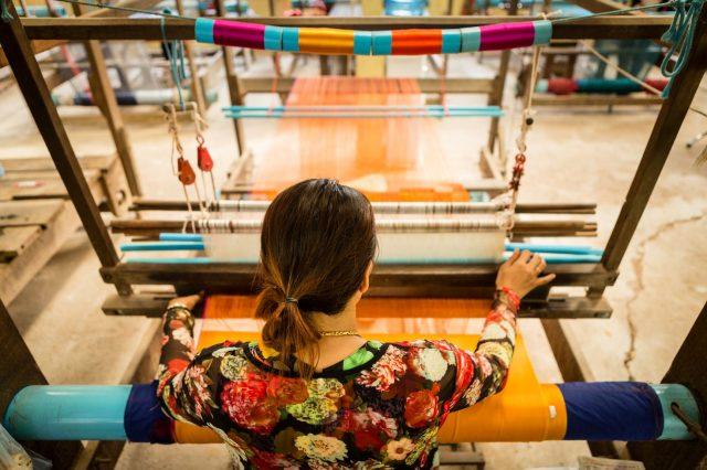 Femme de dos devant un métier à tisser au Cambodge