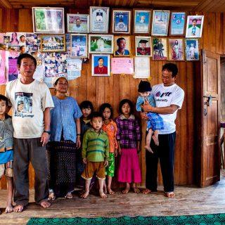 Une Famille dans l'état Kayah. Au mur, des portraits de famille et des diplômes scolaires.